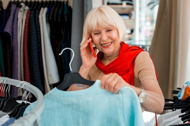 Partager des émotions. femme à la mode aux cheveux gris ravie de parler avec son amie tout en tenant une robe d'été récemment choisie et se sentir satisfait