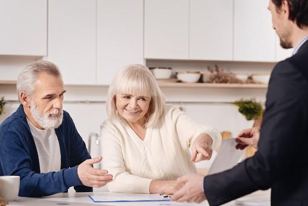 Partager des opinions. heureux vieux couple agréable assis à la maison et discuter de l'accord avec l'agent immobilier tout en échangeant des opinions