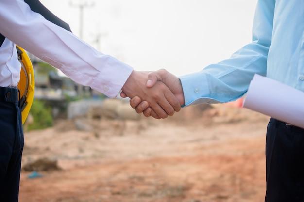 Partenaire commercial serrer la main accord projet construction immeuble immobilier