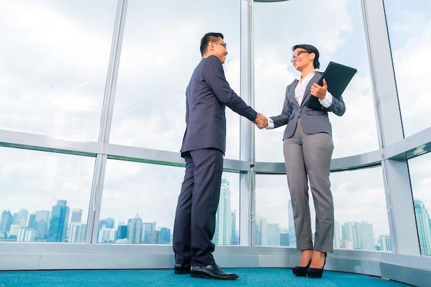 Partenaires d'affaires asiatiques se serrant la main