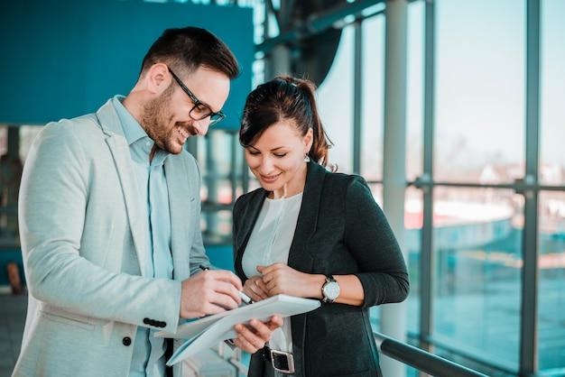 Partenaires d'affaires confiants parler dans un immeuble de bureaux.
