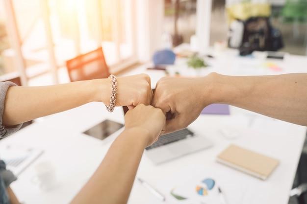 Partenaires d'affaires donnant un coup de poing à fist bump pour mener à bien notre mission ensemble