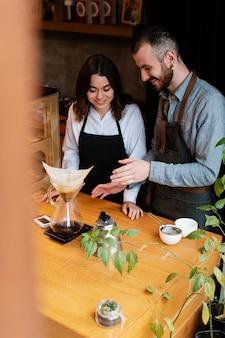 Partenaires de café angle élevé travaillant