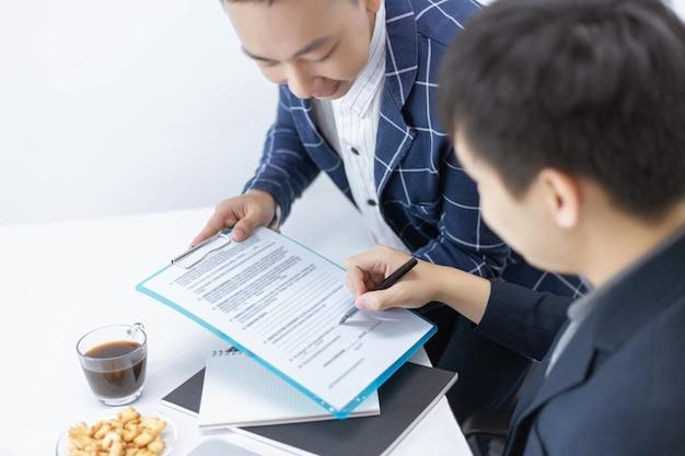 Les partenaires commerciaux conçoivent un jeune entrepreneur masculin signant une signature sur le contrat avec une grande entreprise.