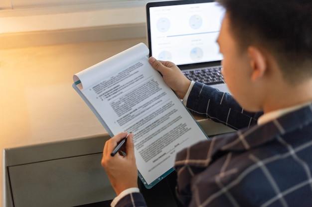 Les partenaires commerciaux conçoivent un jeune homme d'affaires révisant le résumé des ventes du mois dernier s'affichant sous forme de document.