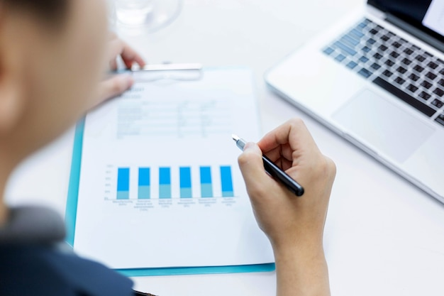 Les partenaires commerciaux conçoivent un jeune homme d'affaires tenant un stylo pointant sur le résumé des bénéfices du mois dernier affiché sous forme de document.