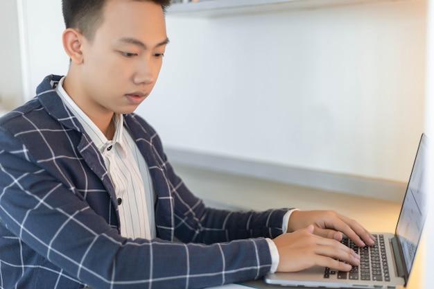 Les partenaires commerciaux conçoivent un jeune homme d'affaires utilisant un ordinateur portable révisant le résumé des ventes annuelles.