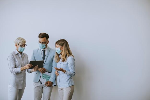 Partenaires commerciaux debout et regardant les résultats commerciaux au bureau tout en portant des masques faciaux en tant que protection antivirus