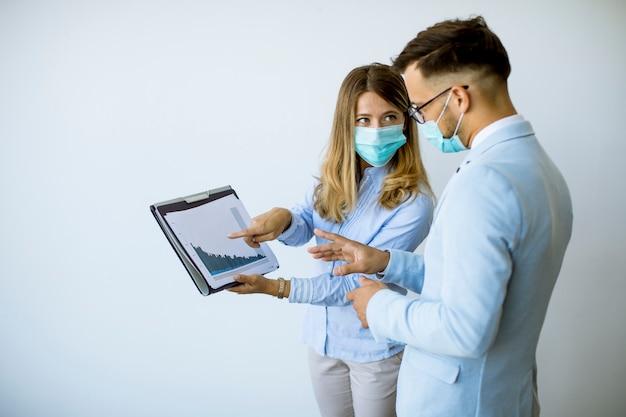 Partenaires commerciaux debout et regardant les résultats de l'entreprise au bureau tout en portant des masques faciaux une protection antivirus