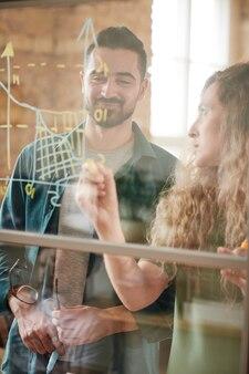 Partenaires commerciaux dessinant un graphique sur un mur de verre et en discutant pendant le travail au bureau