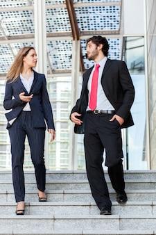 Partenaires commerciaux discutant ensemble sur des escaliers en plein air