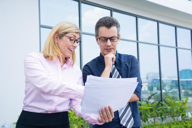 Les partenaires commerciaux du contenu discutent des documents en dehors du bureau.