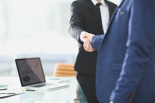 Partenaires commerciaux de poignée de main debout à côté du bureau