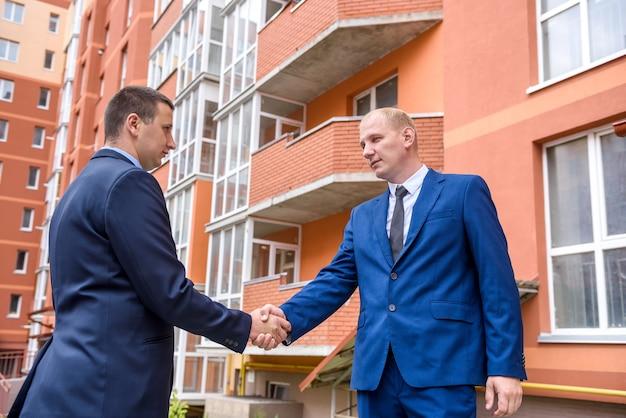 Partenaires commerciaux poignée de main près d'un immeuble de bureaux à l'extérieur