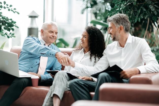 Partenaires commerciaux se serrant la main lors d'une réunion de travail