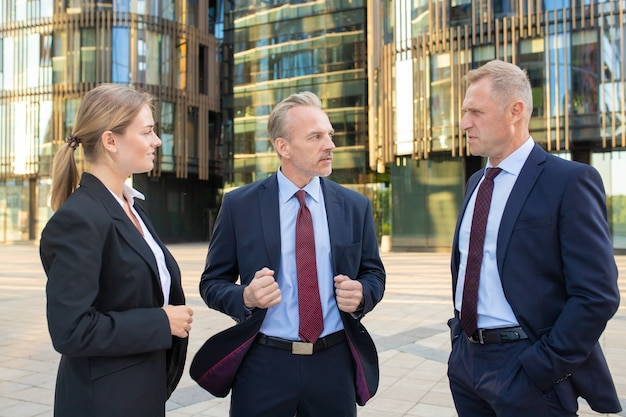 Partenaires commerciaux sérieux et confiants discutant du projet à l'extérieur, debout et parlant avec la construction de la ville en arrière-plan. concept de partenariat et de communication