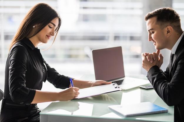 Partenaires commerciaux signant un contrat au bureau. femme signe un contrat au bureau.