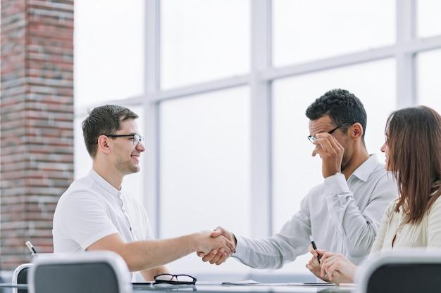 Partenaires commerciaux souriants se serrant la main pendant la réunion