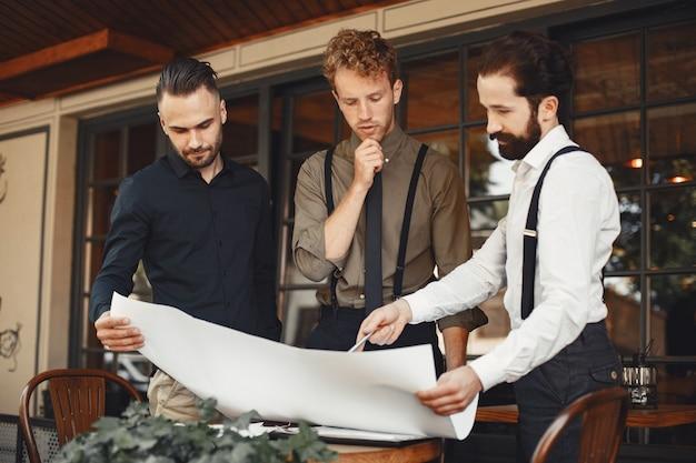Les partenaires commerciaux tiennent des discussions. les hommes en costume parlent. homme en bretelles avec une barbe.