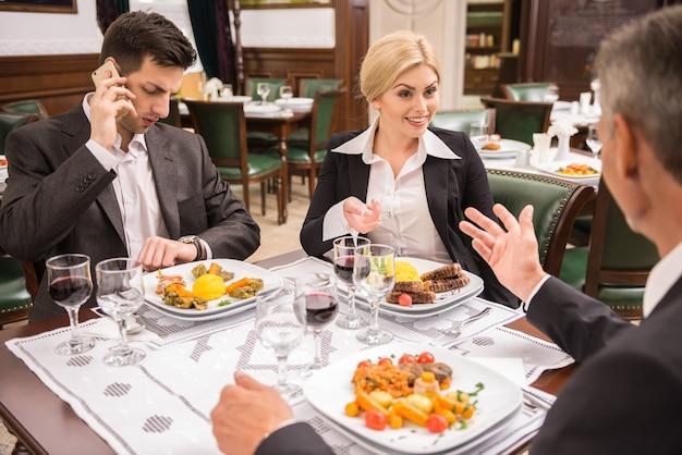 Partenaires en costume discutant contrat lors d'un déjeuner d'affaires.