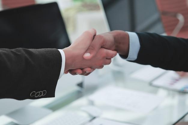 Partenaires financiers de poignée de main au-dessus d'un bureau dans le bureau