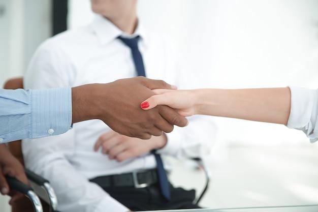 Partenaires financiers solides se serrant la main sur un bureau