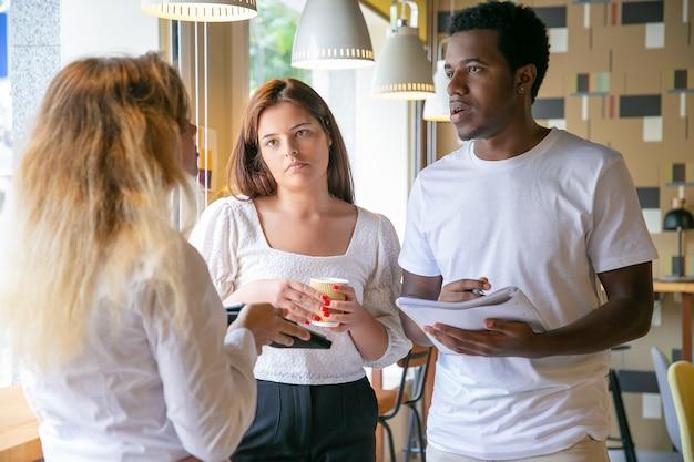 Partenaires multiethniques debout et discutant du projet