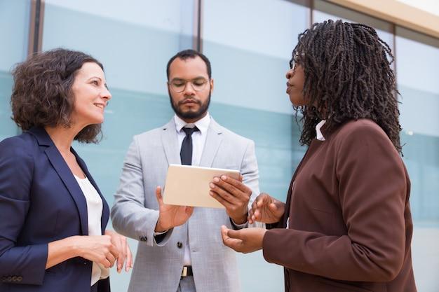 Des partenaires multiethniques discutent d'un projet à l'extérieur