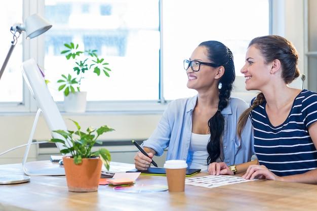 Partenaires souriants travaillant ensemble sur ordinateur et numériseur