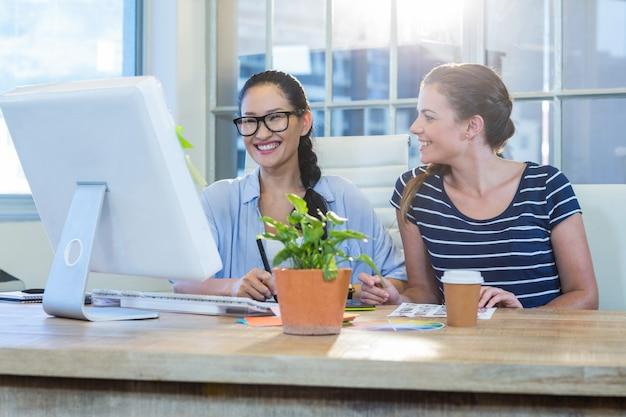 Partenaires souriants travaillant ensemble avec des photographies et numériseur