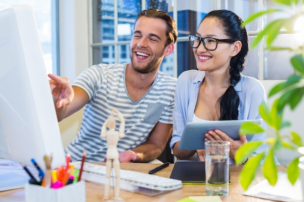 Partenaires souriants travaillant ensemble sur tablette et ordinateur