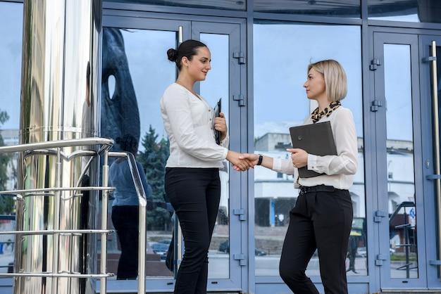 Partenariat. deux jeunes dames d'affaires poignée de main à l'extérieur de l'immeuble de bureaux