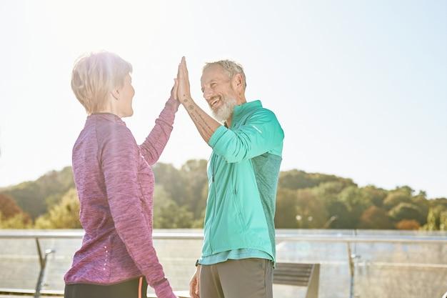 Partenariat famille heureuse couple homme et femme mûrs en vêtements de sport donnant cinq après avoir