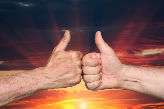 Partenariat. thumbs up signe sur fond de ciel coucher de soleil