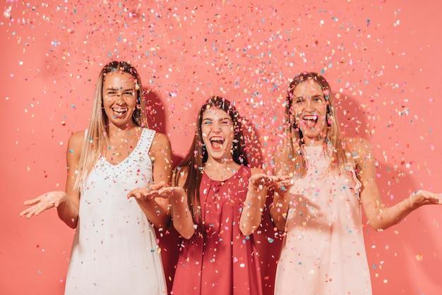 Parti amis posant avec des confettis