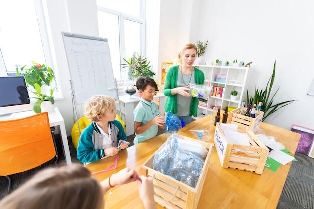 Participation au tri. enfants mignons et intelligents se sentant impliqués dans le tri du plastique lors de la leçon d'écologie