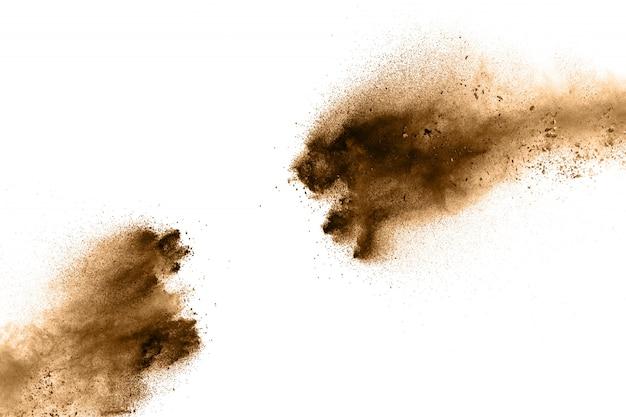 Particules brunes éclaboussées sur fond blanc. poussière brune éclaboussant.