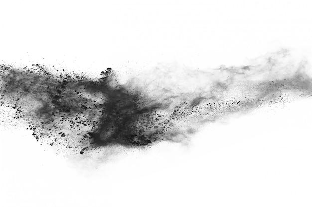 Particules de charbon de bois sur fond blanc, poudre abstraite éclaboussée sur fond blanc.