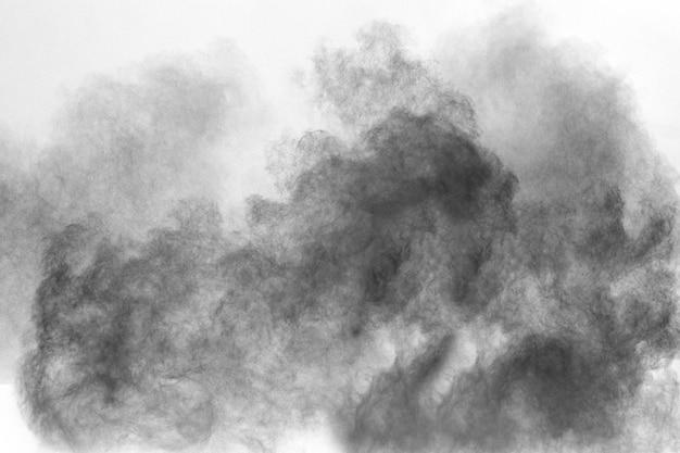 Particules noires éclaboussées sur fond blanc. éclaboussures de poussière de poudre noire.