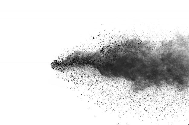 Les particules noires éclaboussent sur fond blanc. la poussière de poudre noire a éclaté.