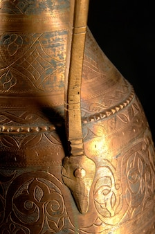 Partie ancienne cruche en métal oriental sur fond sombre. vaisselle en bronze antique