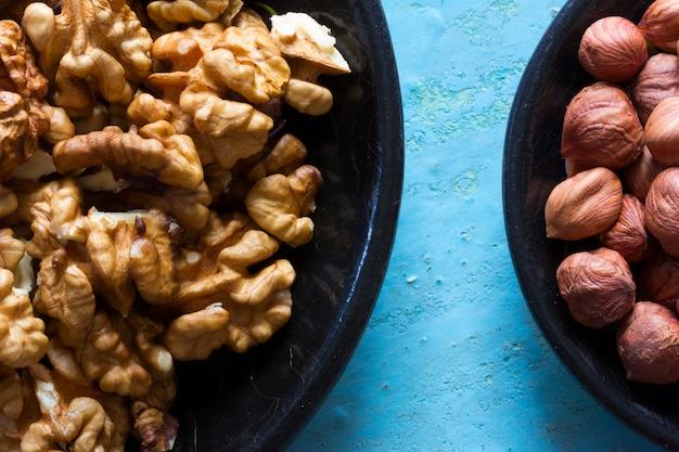 Partie des assiettes rondes en bois avec les noix et les noisettes nettoyées sur un fond bleu.