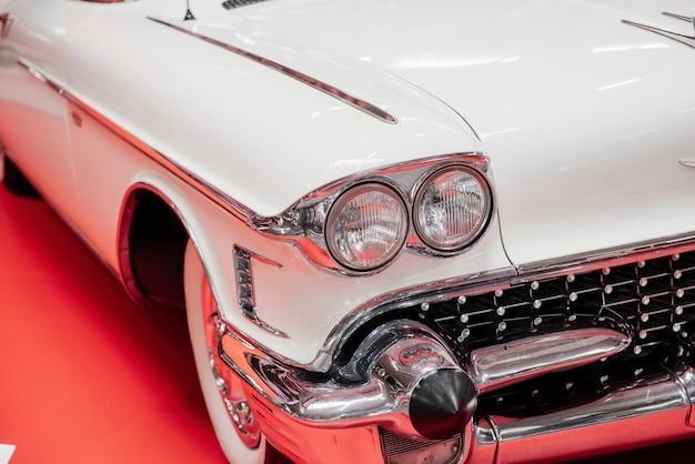 Partie avant de la voiture rétro blanche debout sur la surface rouge