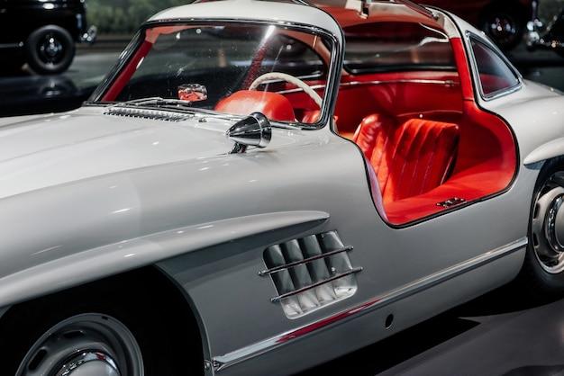 Partie avant d'une voiture vintage blanche avec un salon automobile rouge.