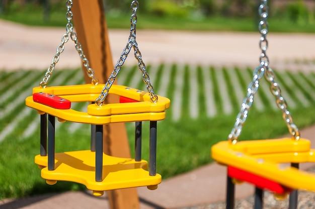 Partie d'une balançoire en bois sur l'arrière-plan flou de la place des enfants