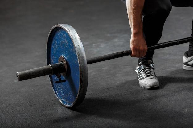 Une partie de la barre de gymnastique avec disque de poids bleu, bras et jambe de l'homme