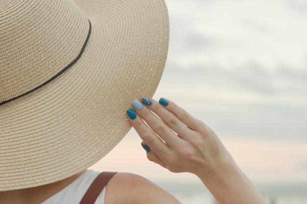 Partie d'un chapeau et d'une main féminine se bouchent. ciel coucher de soleil en arrière-plan
