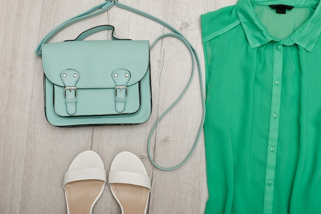 Partie d'un chemisier vert, chaussures blanches, sac à main. concept à la mode. fond en bois
