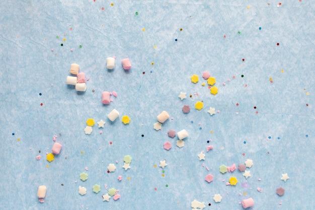 Partie colorée plat poser, joyeux anniversaire, savoureuses douceurs colorées sur fond bleu