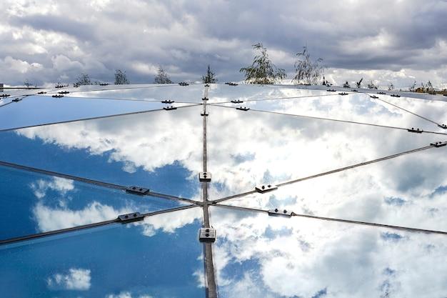 Une partie de la construction en verre qui reflète le ciel bleu.